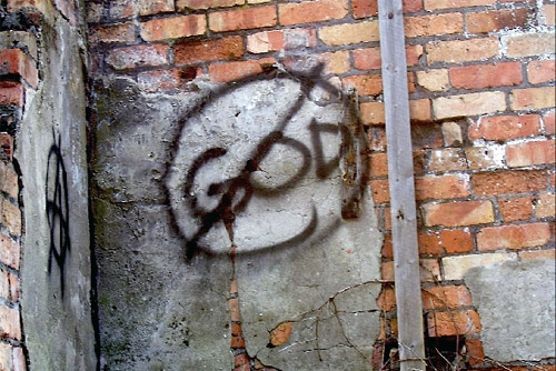 graffiti on a brick wall with the word God crossed out on it